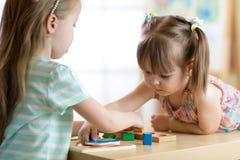 Crianças que jogam com os brinquedos coloridos do bloco Duas meninas das crianças em casa ou centro de guarda Brinquedos educacio imagem de stock