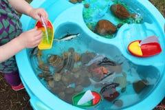 Crianças que jogam com os brinquedos da vida dos barcos e da criatura/oceano do mar em uma tabela de água imagem de stock royalty free