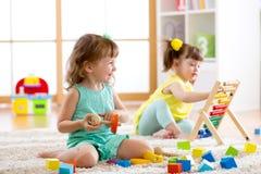 Crianças que jogam com os brinquedos do ábaco e do construtor no centro do jardim de infância, do playschool ou de guarda imagens de stock royalty free