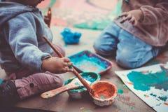 Crianças que jogam com pinturas e pintura à têmpera Imagens de Stock Royalty Free