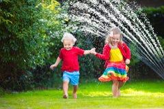Crianças que jogam com sistema de extinção de incêndios do jardim Imagem de Stock