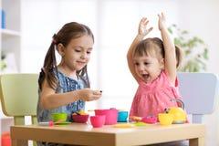 Crianças que jogam com utensílios de mesa plásticos foto de stock royalty free