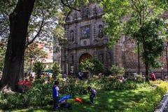 Crianças que jogam em torno de um mercado de rua por uma igreja, Guadalajara, Jalisco, México fotografia de stock royalty free
