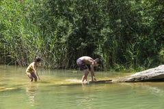 Crianças que jogam em um rio imagem de stock