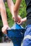 Crianças que jogam em uma torneira da rua imagens de stock royalty free