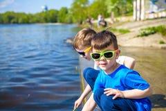 Crianças que jogam fora na natureza: o assento no lago ou o rio suportam areia tocante na água clara no dia morno do verão ou de  Imagem de Stock Royalty Free