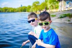Crianças que jogam fora na natureza: o assento no lago ou o rio suportam areia tocante na água clara no dia morno do verão ou de  Imagem de Stock