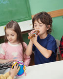 Crianças que jogam instrumentos musicais na sala de aula foto de stock