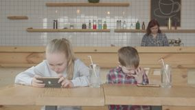 Crianças que jogam jogos onlines em telefones celulares no café vídeos de arquivo