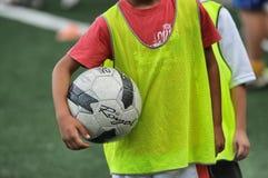 Crianças que jogam na escola do futebol do futebol com instrutor fotografia de stock