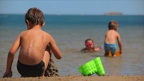 Crianças que jogam na praia com água e a areia