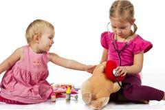 Crianças que jogam o doutor com uma boneca Fotografia de Stock