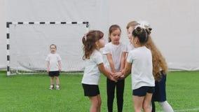 Crianças que jogam o futebol dentro Crianças que fazem um apoio da equipe Gesto da equipe da mão disponível vídeos de arquivo