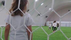 Crianças que jogam o futebol na arena interna do futebol video estoque