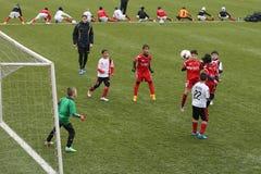 Crianças que jogam o futebol ou o futebol Fotografia de Stock
