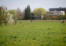 Crianças que jogam o futebol perto da escola Foto de Stock Royalty Free