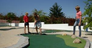 Crianças que jogam o mini golfe no jardim 4k video estoque