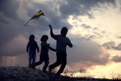 Crianças que jogam o papagaio no prado do por do sol do verão mostrado em silhueta Imagem de Stock Royalty Free
