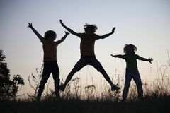 Crianças que jogam o salto no prado do por do sol do verão mostrado em silhueta Imagens de Stock Royalty Free