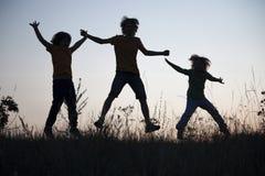 Crianças que jogam o salto no prado do por do sol do verão mostrado em silhueta Fotografia de Stock Royalty Free
