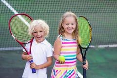 Crianças que jogam o tênis na corte exterior foto de stock royalty free