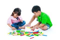 Crianças que jogam os blocos de madeira do brinquedo, isolados no fundo branco Fotos de Stock
