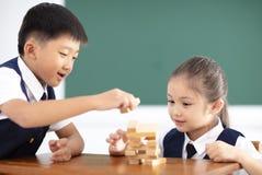crianças que jogam os blocos de madeira na sala de aula Fotografia de Stock