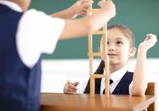 crianças que jogam os blocos de madeira na sala de aula Fotos de Stock