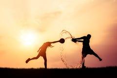 Crianças que jogam a silhueta de Songkran da água do respingo Imagens de Stock Royalty Free