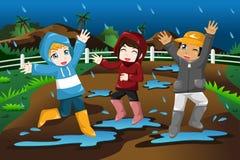 Crianças que jogam sob a chuva Imagens de Stock