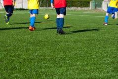 Crianças que jogam um jogo de futebol fotografia de stock