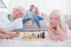 Crianças que jogam a xadrez na frente de seus pais fotografia de stock royalty free