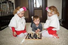 Crianças que jogam a xadrez que encontra-se no assoalho Imagens de Stock Royalty Free
