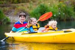 Crianças que kayaking em um rio Foto de Stock Royalty Free