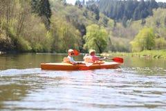 Crianças que kayaking no rio imagens de stock