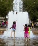 Crianças que lanç a bola na fonte Fotos de Stock