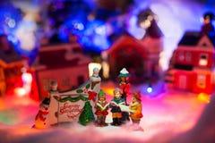 Crianças que leem a Bíblia ao lado do sinal do cumprimento do feriado com a vila nevado do Natal no fundo Scener diminuto de cump Fotos de Stock