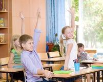 Crianças que levantam as mãos que conhecem a resposta à pergunta Foto de Stock