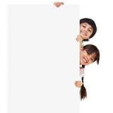 Crianças que levantam com uma placa branca Fotos de Stock