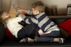 Crianças que lutam sobre de controle remoto Fotos de Stock Royalty Free