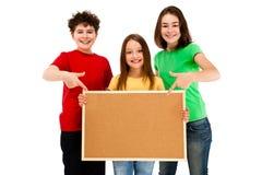 Crianças que mantêm o noticeboard isolado no fundo branco Imagens de Stock