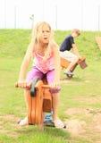 Crianças que montam animais de madeira Fotos de Stock Royalty Free