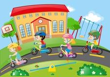 Crianças que montam a bicicleta na estrada Fotografia de Stock