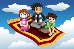 Crianças que montam em um tapete de voo Fotos de Stock