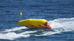 Crianças que montam o barco de banana, velocidade que flutua, atração da água do verão no lento-mo vídeos de arquivo