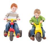 Crianças que montam triciclos dos miúdos fotografia de stock