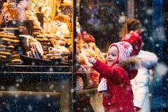 Crianças que olham doces e pastelaria no mercado do Natal fotografia de stock royalty free