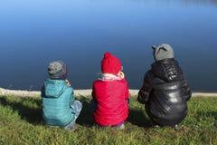 Crianças que olham na água, opinião da parte traseira imagem de stock royalty free