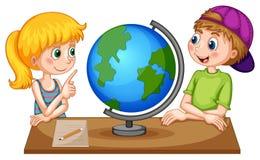 Crianças que olham o globo na tabela Fotografia de Stock