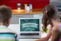 Crianças que olham um computador com ícones da escola na tela Imagem de Stock